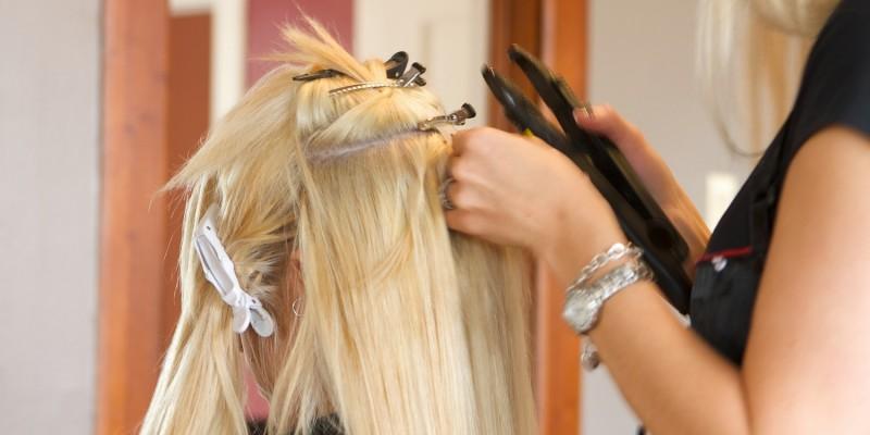 Friseurin bringt Extensions an